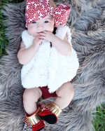 Azlyn sporting the cutest IG outfit including bow from StitchHemBowtique, Romper from HeartOfViolet and Vest/Mocc Boots from GraciousMay